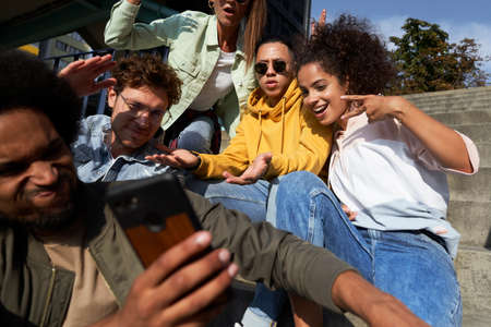 Young people gesturing and doing selfie together outdoors