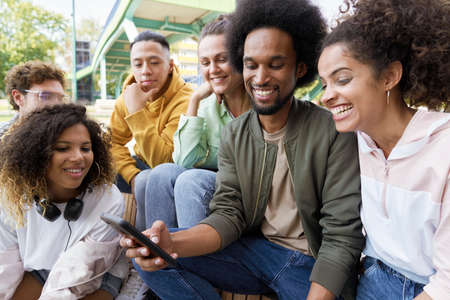 Young people sitting and staring at cell phone