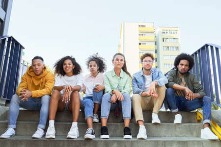 Group of young people sitting in a row on the stairs