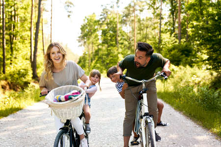 Playful family having fun on a bicycles in the woods