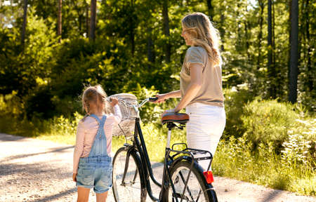 Rear vier of mother and daughter pushing bicycle in the forest