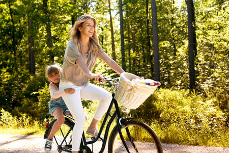 Mother and daughter riding a bicycle in the forest Фото со стока