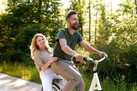 Playful couple having fun on a bike in the woods Фото со стока