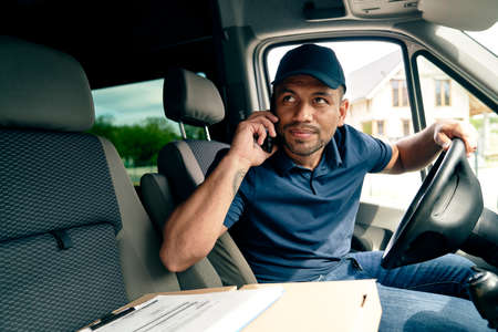 Driver with package looking away while sitting in truck