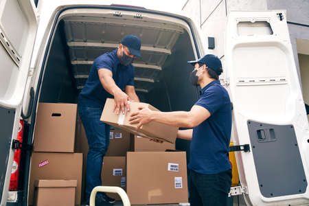 Bottom view of couriers unloading packages during a pandemic Фото со стока