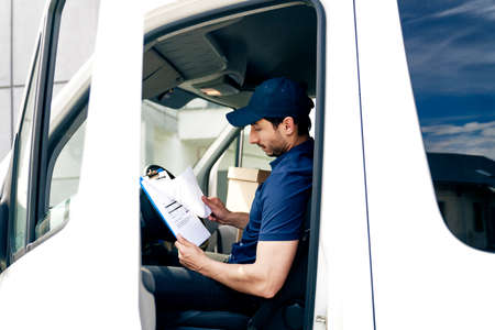Courier sitting in the car and looking at documents Фото со стока