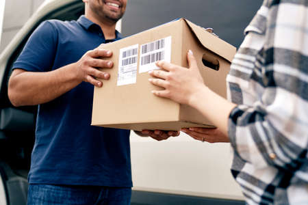 Close up of courier giving a package to a customer