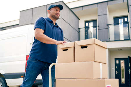 Bottom view of courier going with packages on a hand truck Фото со стока