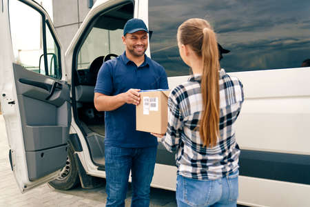 Smiling courier handing a package to a woman