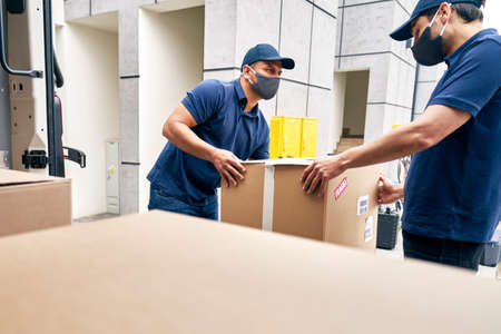 Couriers unloading packages from a delivery truck during a pandemic