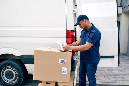 Courier standing with packages and looking at documents