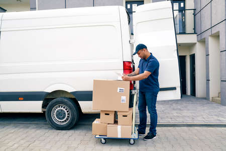 Courier with packages on a hand truck looking at documents
