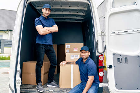 Portrait of couriers in a trunk full of parcels