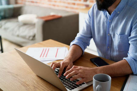 Close up unrecognizable man working on a laptop at home
