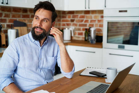 Smiling man using headphones during working at home Фото со стока