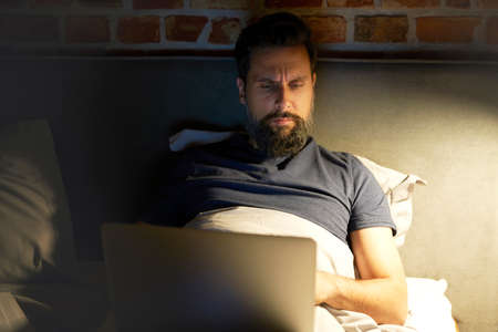 Front view of man using laptop in bed Standard-Bild