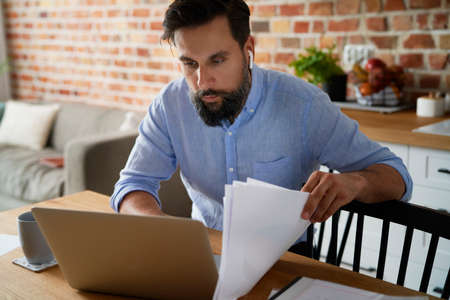 Man with documents working on laptop at home