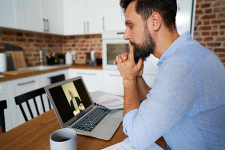 Rear view of business conference call over laptop