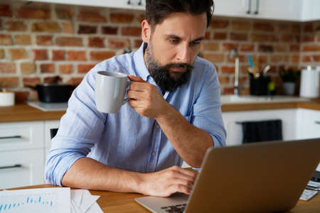 Serious man holding coffee cup and working at home