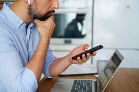 Side view of man holding phone during home office