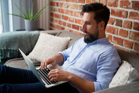 Man in a shirt sitting on couch and using laptop