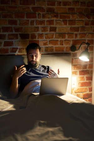 Man working late in bed Standard-Bild