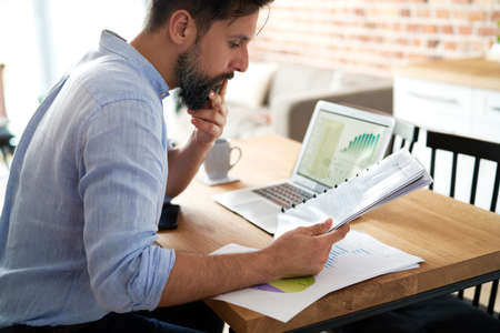 Man analyzing documents while working from home Standard-Bild