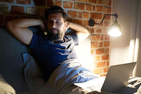 Overworked man working late in bed