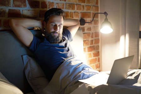 Tired man with laptop in bed