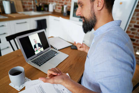 Satisfied man talking to boss on web meeting
