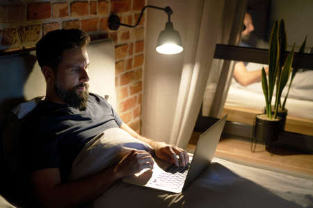 Man lying in bed and working at night