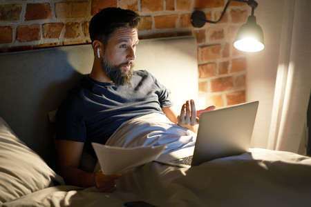 Man lying in bed during video conference at night