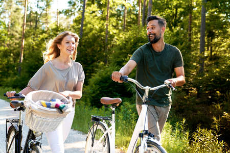 Couple pushing bicycle on a sunny day Standard-Bild