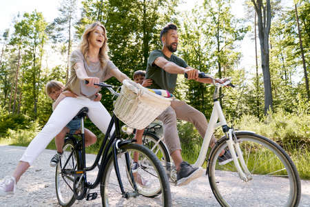 Exuberant family riding bicycles in the forest