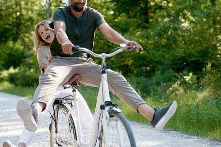 Close up of exuberant couple sharing a bicycle