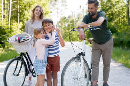 Family with playful children while bike ride in the woods