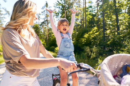 Happy little girl cycling with her mother in the forest Standard-Bild