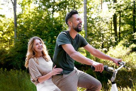 Happy couple having fun on a bike in nature