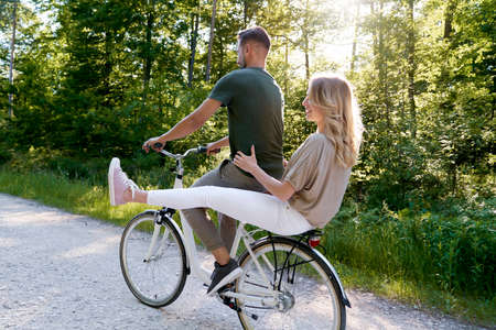 Rear view of couple sharing a bicycle in the forest Standard-Bild
