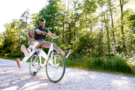 Exuberant couple sharing a bicycle in nature Standard-Bild
