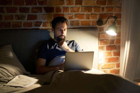 Man lying in bed and using laptop