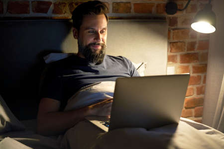 Smiling man lying in bed and using laptop