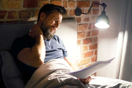 Exhausted man with documents working late in bed