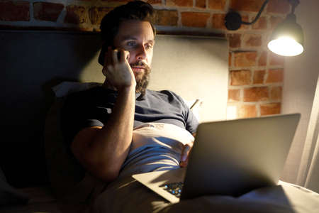 Man call and working in the bedroom at night times Standard-Bild