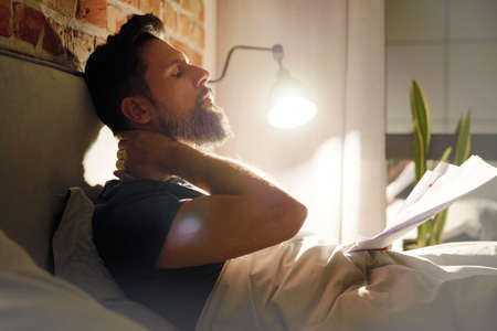 Side view of man with documents working late in bed Standard-Bild
