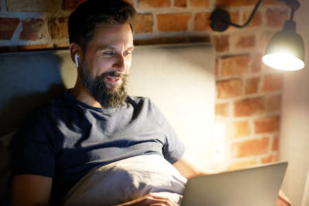 Smiling man with laptop in bed at night Standard-Bild