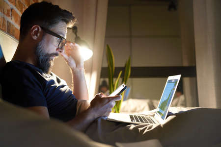 Side view of man with glasses working in bed at night Standard-Bild