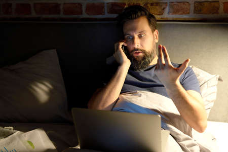 Man talking on the phone in bed at night Standard-Bild