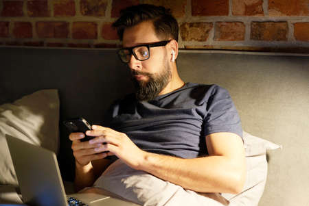 Man with glasses using phone and laptop in bed