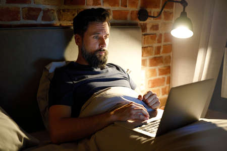 Tired man lying in bed and working using laptop
